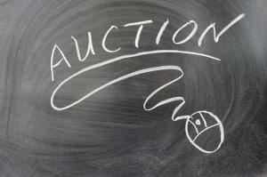 Auction word and mouse symbol on chalkboard representing online auctions for selling land